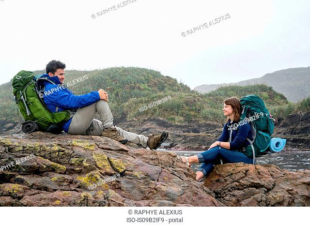 Young couple with backpack, sitting on rocks, Constant Bay, Charleston, South Island, New Zealand