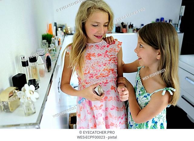 Two girls applying perfume in bathroom