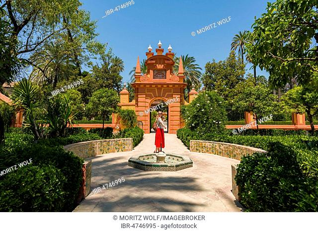 Young woman in red dress in the gardens of the Alcazar, fountain, Royal Palace of Seville, Sevilla, Spain