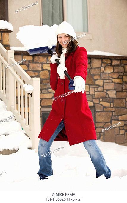 USA, Utah, Lehi, Portrait of young woman throwing snow using snow shovel