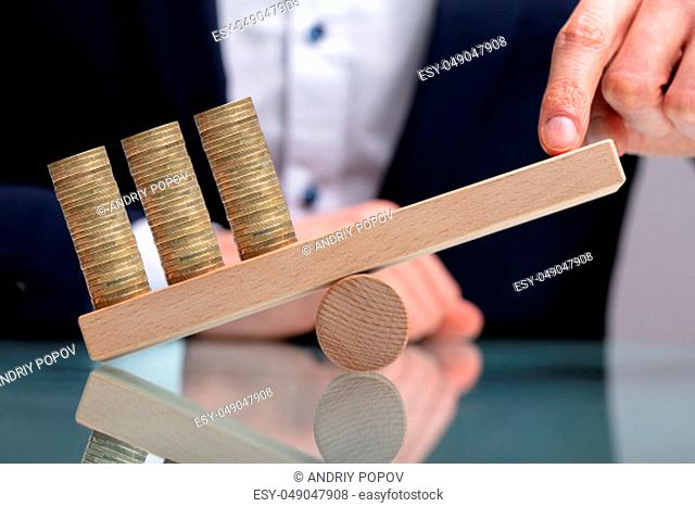 Businessman Balancing Stacked Coins With Finger On Wooden Seesaw Over Reflective Desk