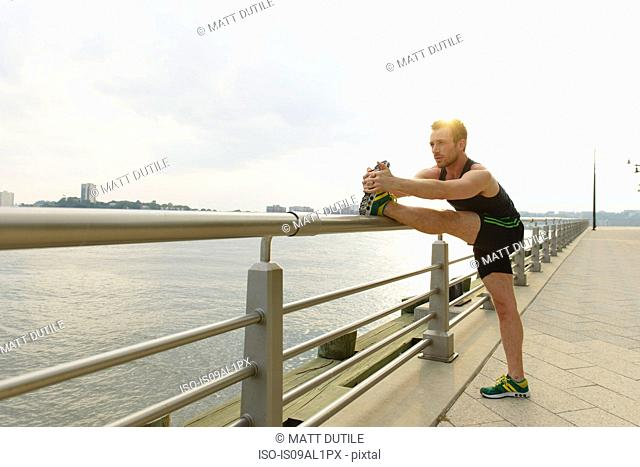 Young man touching toes on riverside railings