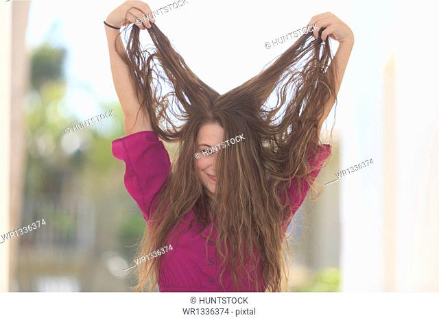Smiling young woman holding her long hair in the air