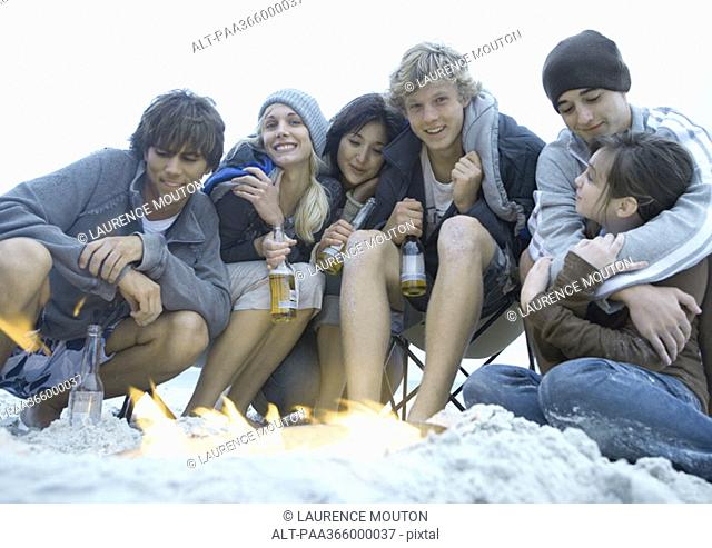 Group of young adult friends sitting around campfire