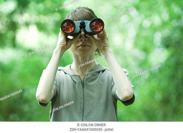 Woman looking through binoculars, front view