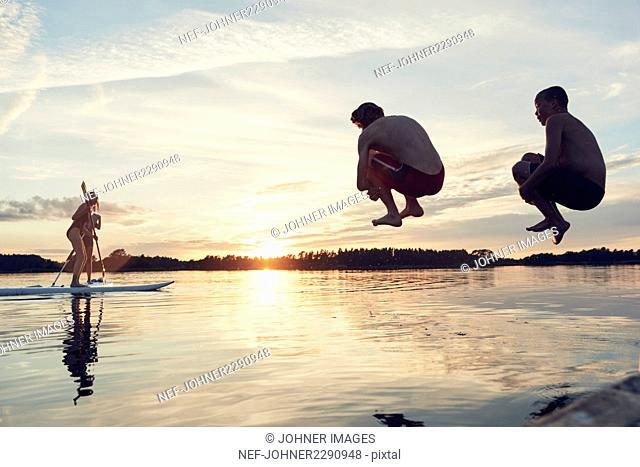 Boys jumping into lake