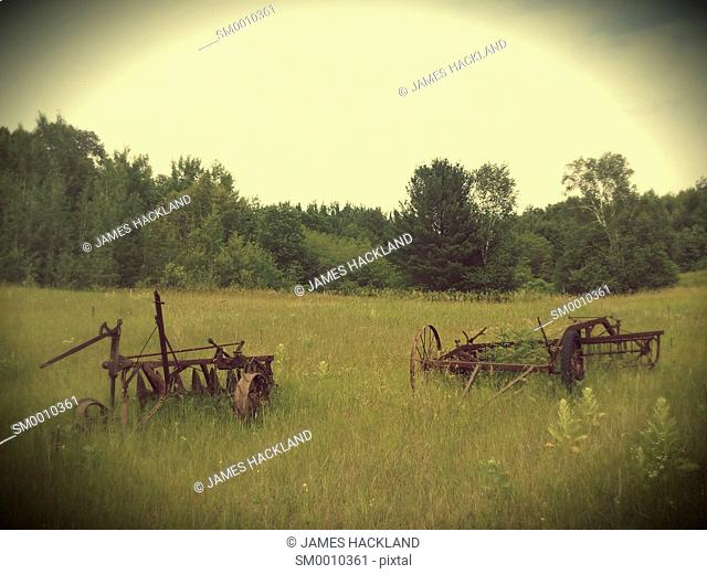 Old farm equipment from a bygone era sitting in a a field of overgrown grass. East Gwillimbury, Ontario, Canada