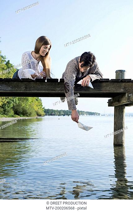 Young man woman playing paper boat jetty
