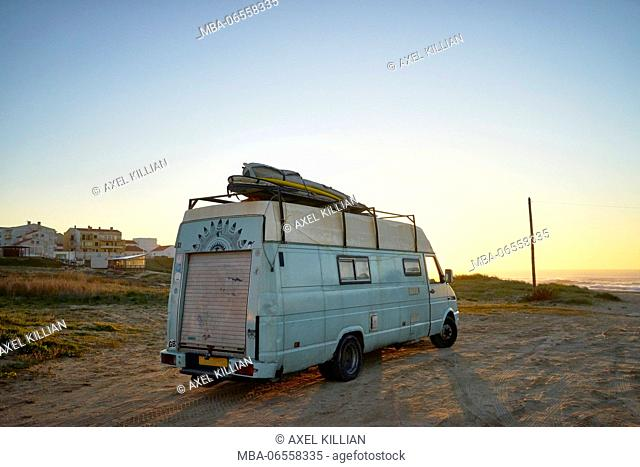 Old camper on the beach, surfboard on the roof