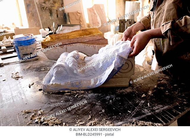 Caucasian artist lifting mold from plaster