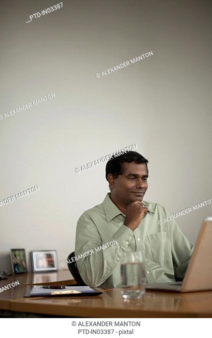 Singapore, Businessman using laptop at work