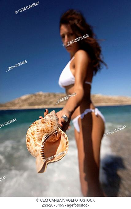 Woman holding a winkle in her hand, Naxos, Cyclades Islands, Greek Islands, Greece, Europe