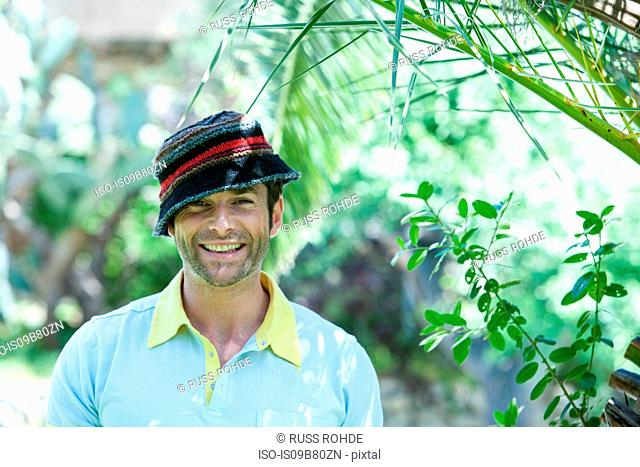 Portrait of happy mid adult man wearing hat in garden