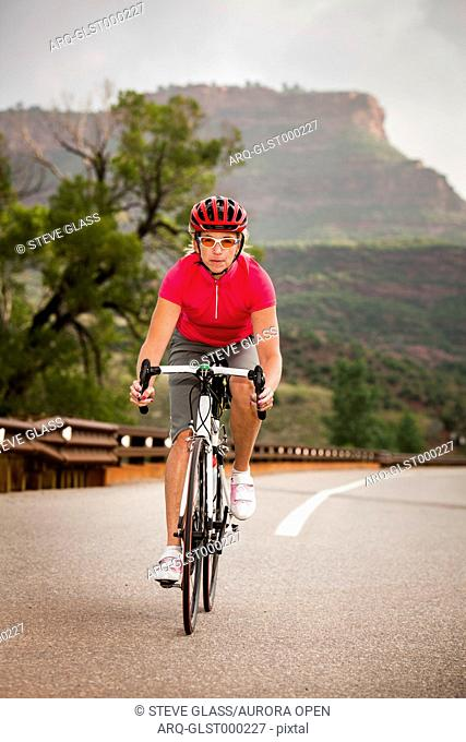 Women road cyclist rides her road bike, on Co Rd 38 E heading west, just west of Horsetooth Mountain Park
