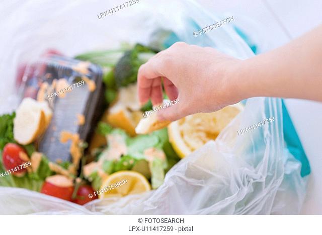 Woman throwing garbage in bin