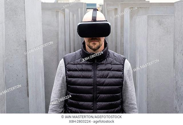 Man wearing Virtual Reality (VR) goggles out door in Berlin, Germany