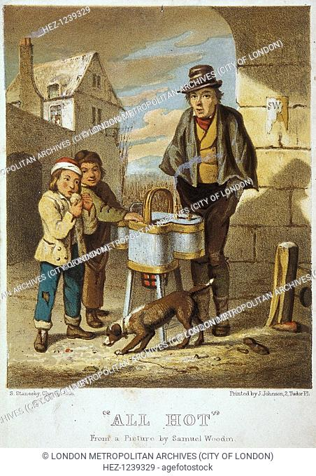 'All Hot'. A baked potato seller with two boys. Standing on a street corner, one of the boys is eating a baked potato, while a dog stands in front of them...