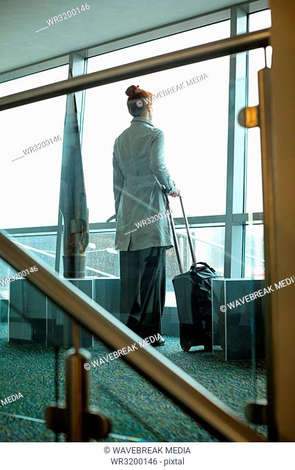 Businesswoman standing with luggage in hotel room