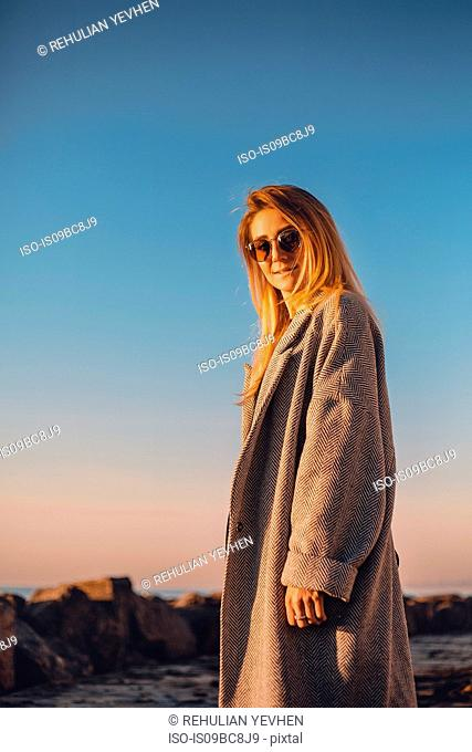 Portrait of woman wearing sunglasses and winter coat looking at camera smiling, side view, Odessa, Odeska Oblast, Ukraine, Eastern Europe
