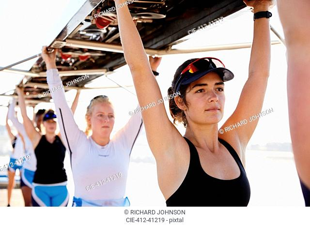 Confident, determined female rowing team lifting scull overhead