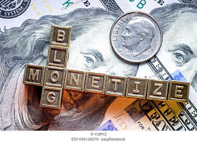 monetize blog phrase made from metallic letter blocks over dollar banknotes