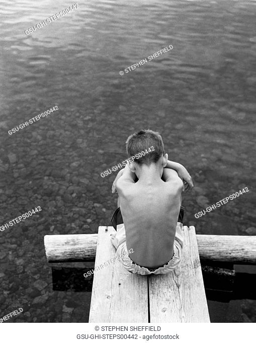 Rear View Portrait of Sad Boy Sitting Hugging His Knees at End of Dock on Lake, High Angle View
