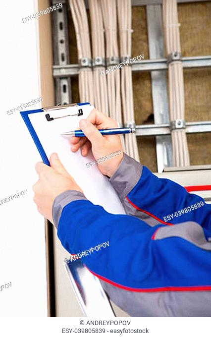 Portrait of young construction worker writing on clipboard