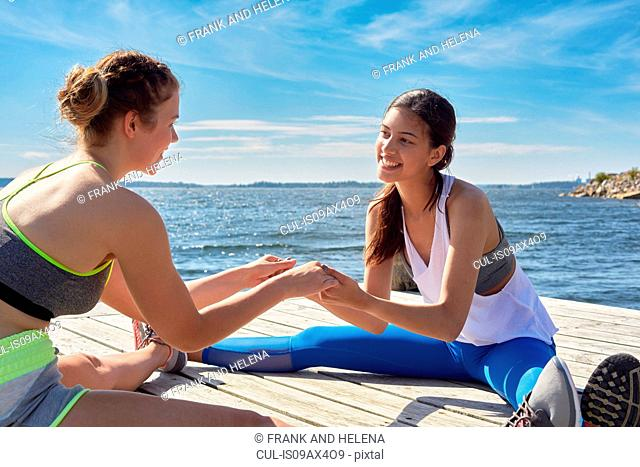 Women wearing sports clothes sitting on pier holding hands face to face smiling
