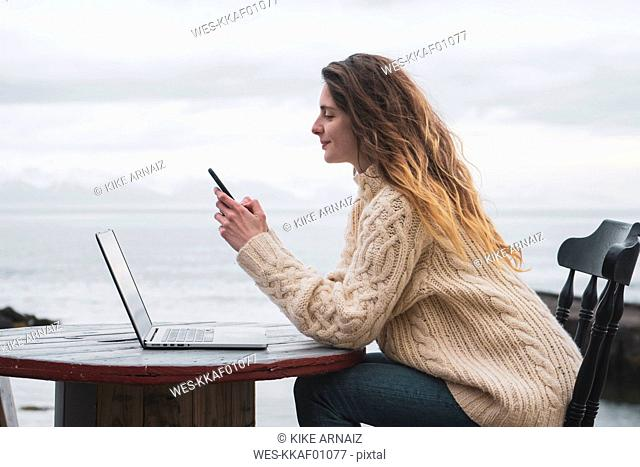 Iceland, woman using laptop and cell phone at the sea
