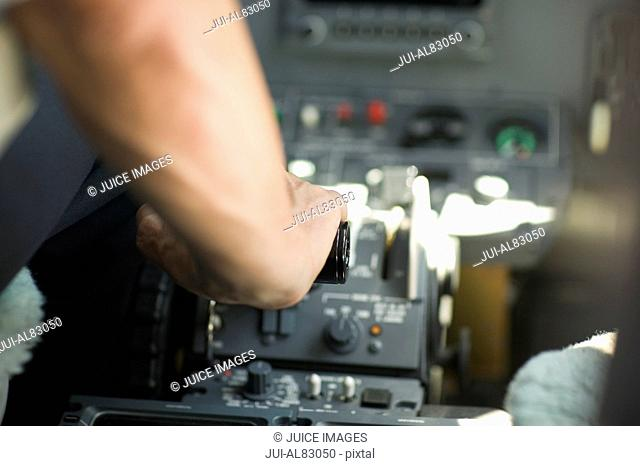 Close up of pilot's arm in cockpit of airplane