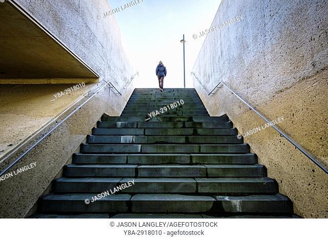 A woman walking up stairs, Brug van Vroenhoven, Reimst, Limburg, Vlaanderen (Flanders), Belgium