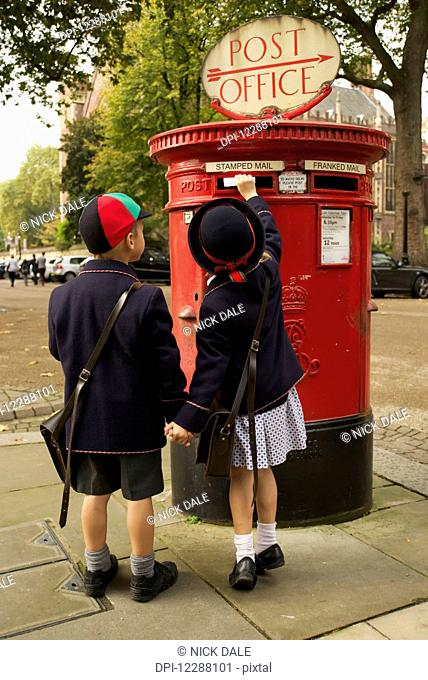 Sister and brother holding hands posting letter; London, England
