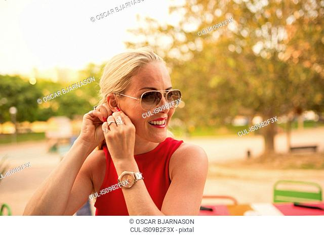 Woman in red putting in earring at park, Alicante, Spain