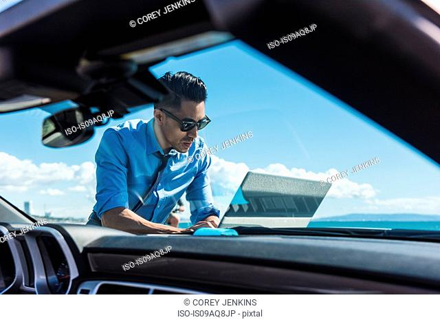Young businessman at coast parking lot using laptop on car hood
