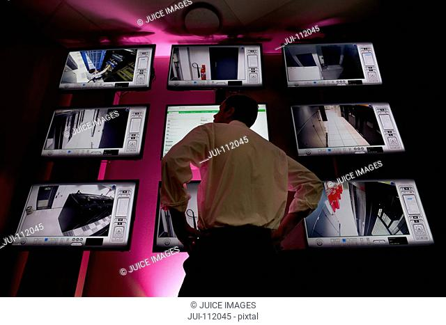 Security guard monitoring CCTV screens in data centre