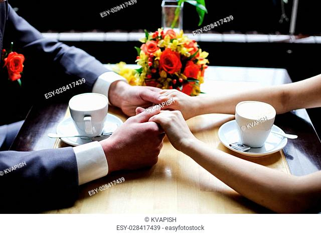 Couple holding hands in the restaurant and two cups of coffee