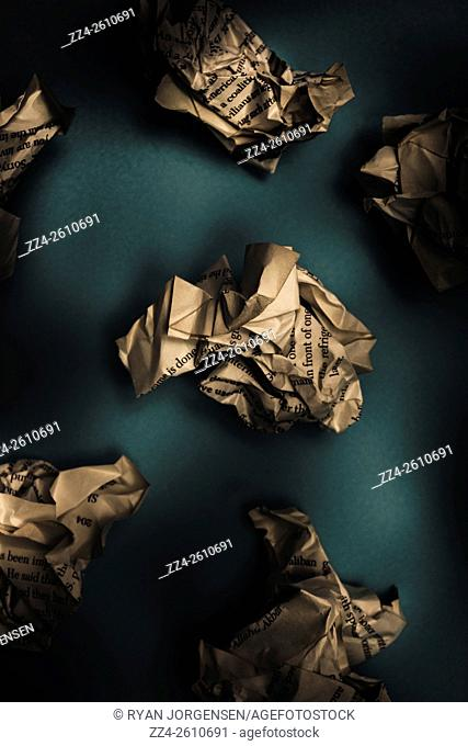 Business and literature conceptual of crumpled paper balls lying on dark blue background. Writers block