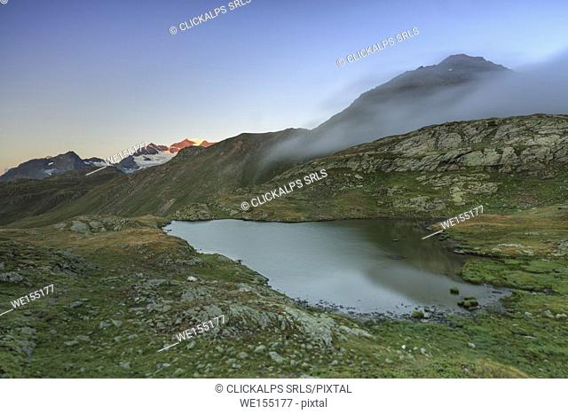 Mist at sunrise on the alpine lake in the background the snowy peaks Minor Valley Alta Valtellina Livigno Lombardy Italy Europe