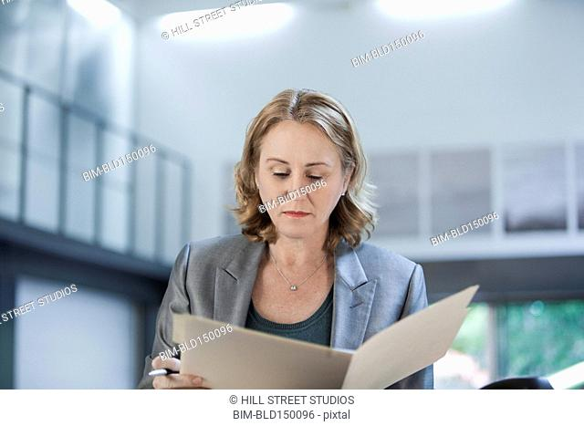 Caucasian businesswoman looking at paperwork
