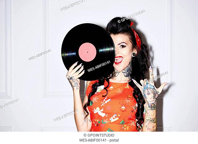 Portrait of tattooed woman with record showing Rock And Roll Sign