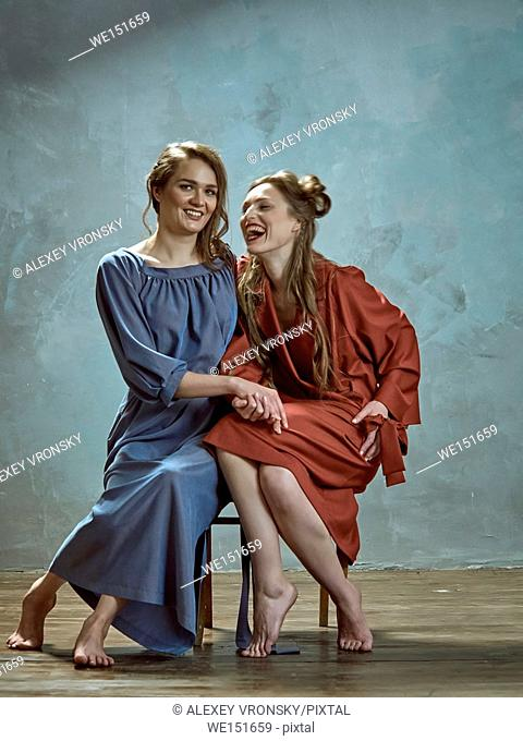 Photographing fashion collections of clothes in the Studio. Photos were taken opposite the dark gray walls. Two young pretty girls sitting on the same chair