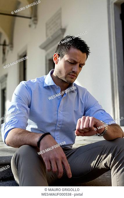 Man sitting outdoors checking the time