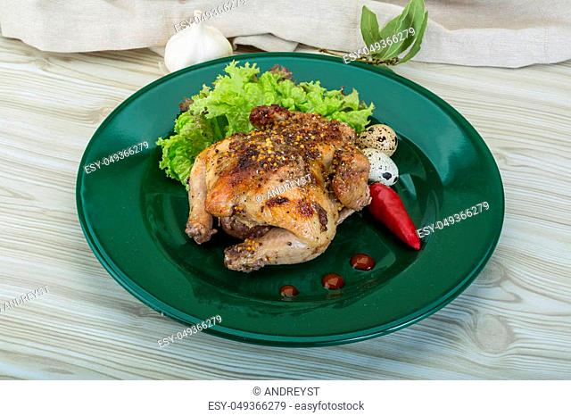 Grilled quail with eggs and spices on wooden background