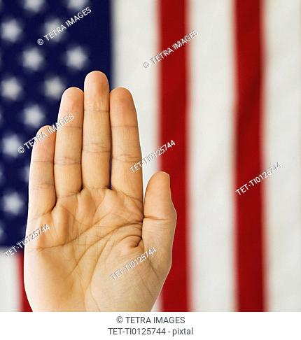 Man's hand up in front of American flag