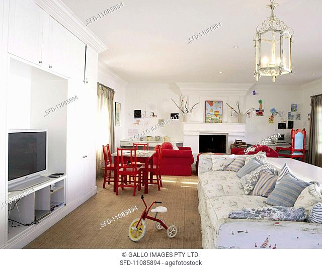 An open living space with a sofa set, TV unit and play area for children