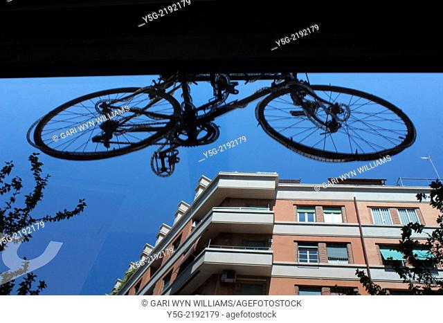 hanging bike reflection in shop window in rome italy