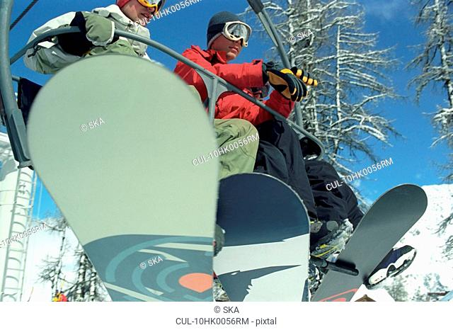 2 males riding on chair lift
