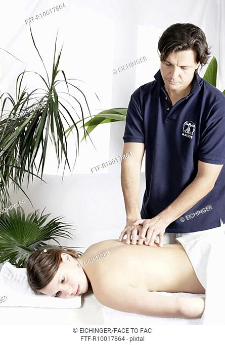 Young woman having back massage by man