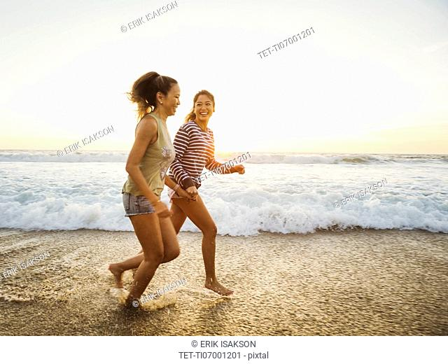 Mother and daughter jogging along beach