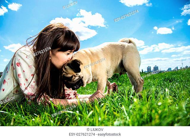 Girl kissing dog breed Mops